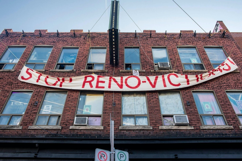 """Photograph of the 2 storey building at 54 Kensington avenue taken from the sidewalk looking up. A banner with """"Stop Renovictions! """" hangs on the front."""